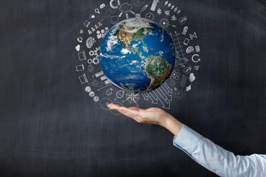 Businesswoman holding earth front of blackboard