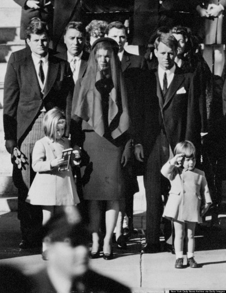 Relinquishing his mother's hand, John F. Kennedy Jr. salutes
