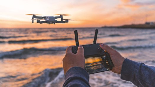 Someone is seen flying a drone on a beach over the ocean.
