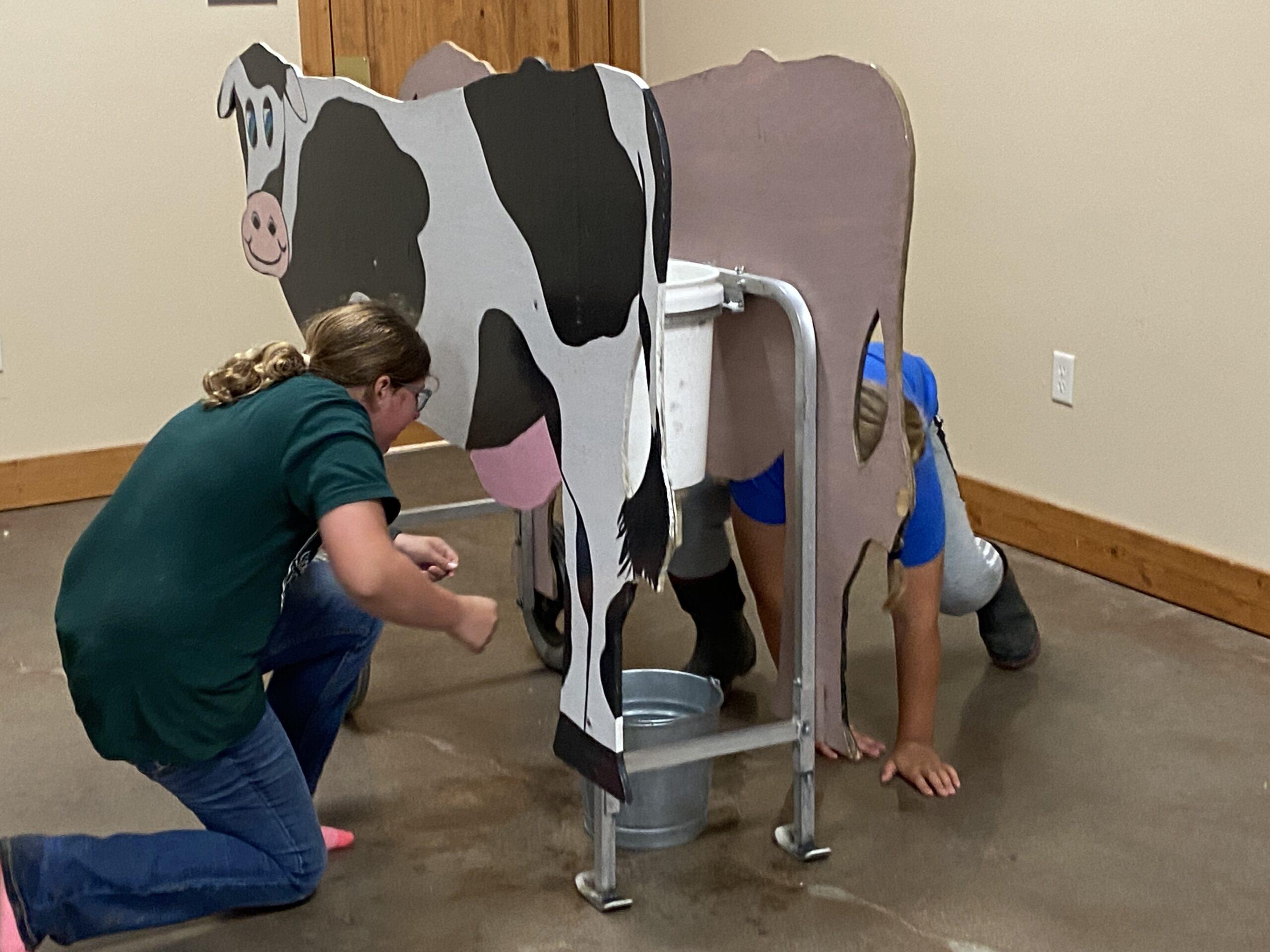 Kids milking a model cow