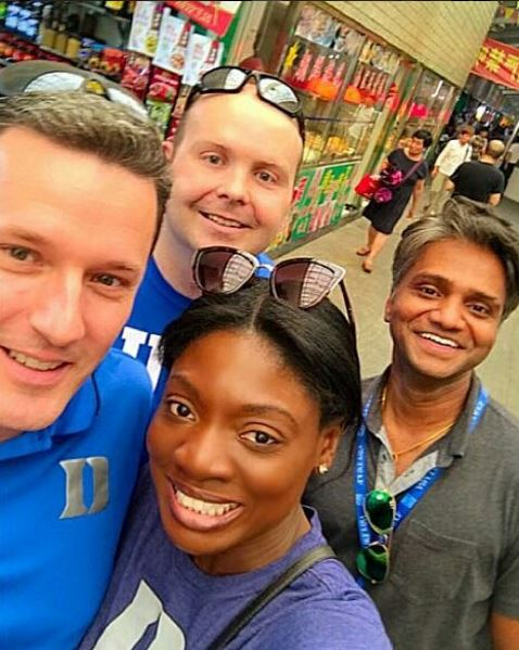 classmates pose in the market, during a day in the life of a Global Executive MBA student