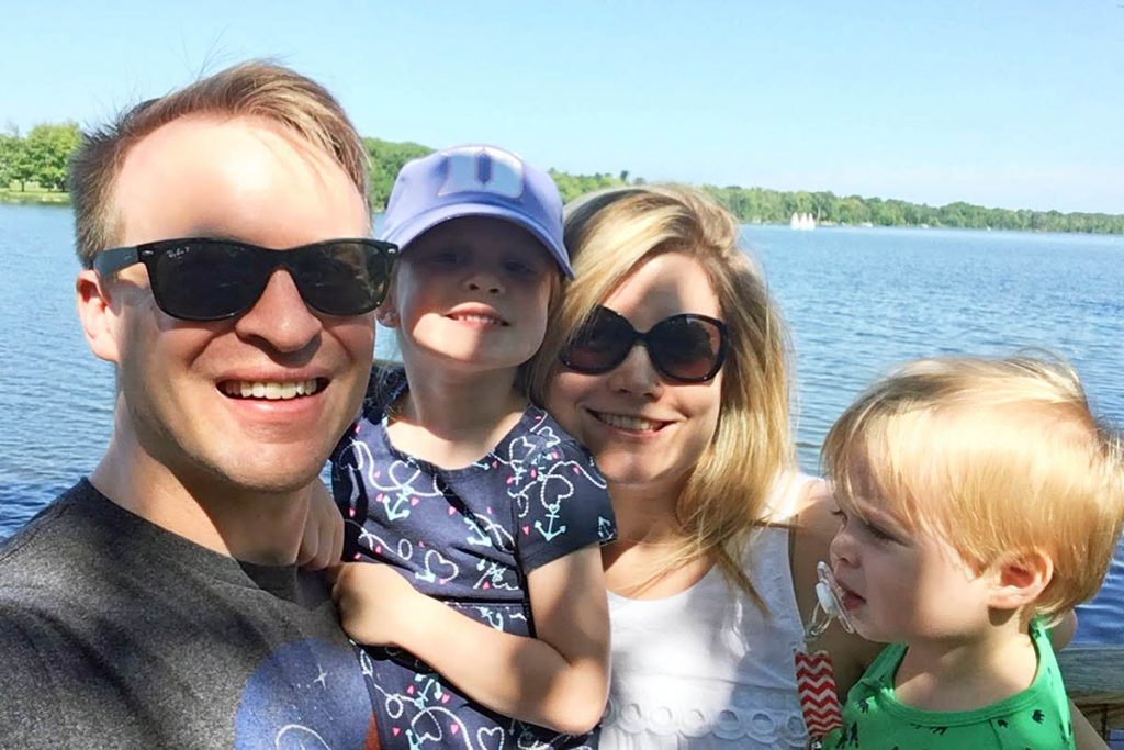 Jamie, his wife and two small kids posing for a selfie at a lake; family life