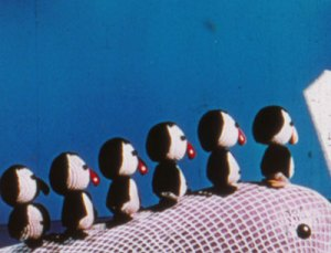six minature penguins climb a whale's back in a still frame from an animated color film
