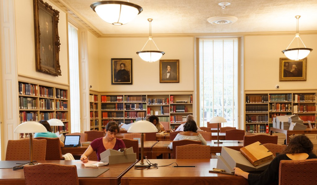 Readers study and look at materials in Houghton Library's reading room.