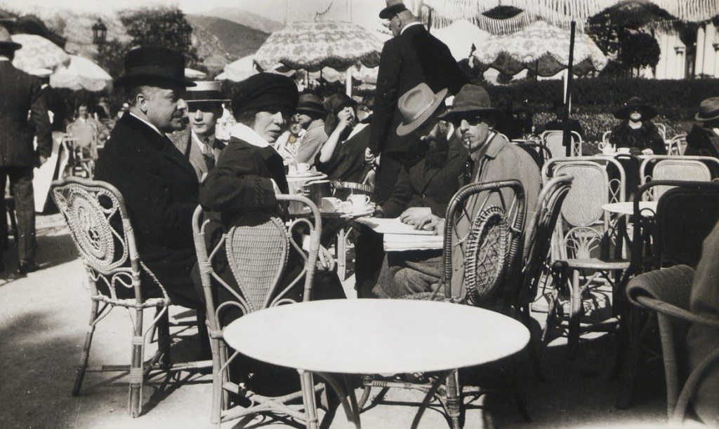 Black and white photo of Serge Diaghilev, Boris Kochno, Bronislava Nijinska, Ernest Ansermet, and Igor Stravinsky sitting at an outdoor café in Monte Carlo.