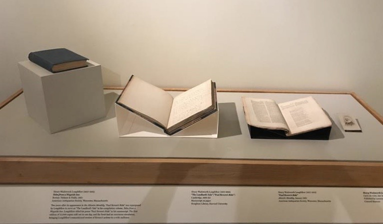 A museum case displays three books and a small card under glass.