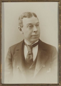 A man in suit, waistcoat, and black tie, clean-shaven with his hair parted in the middle.