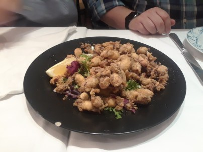 Fried calamari with leafy greens and lemon at La Gloria de Montera restaurant