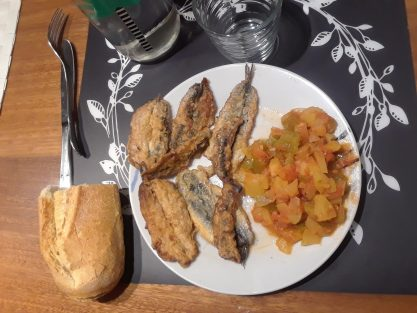 Fried fish, pisto (vegetable mixture with tomatoes and peppers), and bread