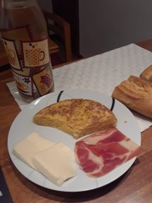 Classic spanish tortilla (potatoes and egg omelet), spanish ham, slices of cheese, and bread