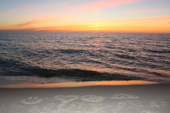 smiley face, heart, peace sign, and sun drawn in the sand by the water at sunset