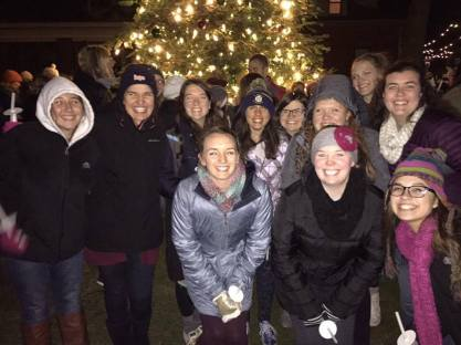 A group of college students in front of a Christmas tree
