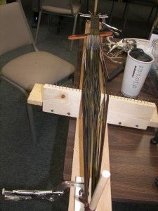 A card loom--simply two pegs to anchor the warp and a spreader to help keep the threads in order