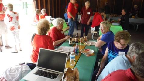 2d cousin Marilyn, at far end of the table on left.  Red shirts were descendants of Daniel, Blue shirts descendants of Ernst.