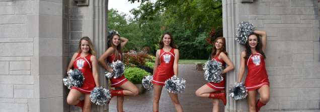 5 dance team members with pom poms and red uniform