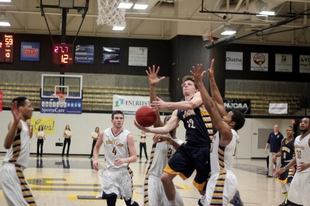 Danzel Wright tries to score shrouded by a forest of Scottie defenders against Highland Community College at home. Wright and the Cavs won 71- 69 on sophomore night.
