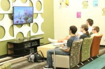 Students play video games in the student lounge on the third floor of the Commons building.