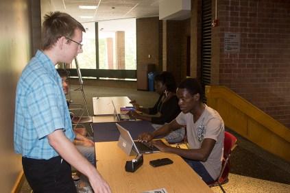Student Senate President John Rives assists with the Student Senate voting.
