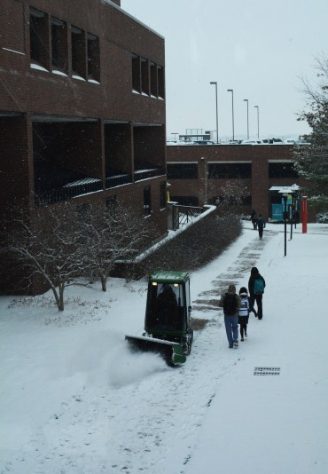 Campus services works to remove snow from the sidewalks. Photo by Andrew Hartnett/ The Campus Ledger.