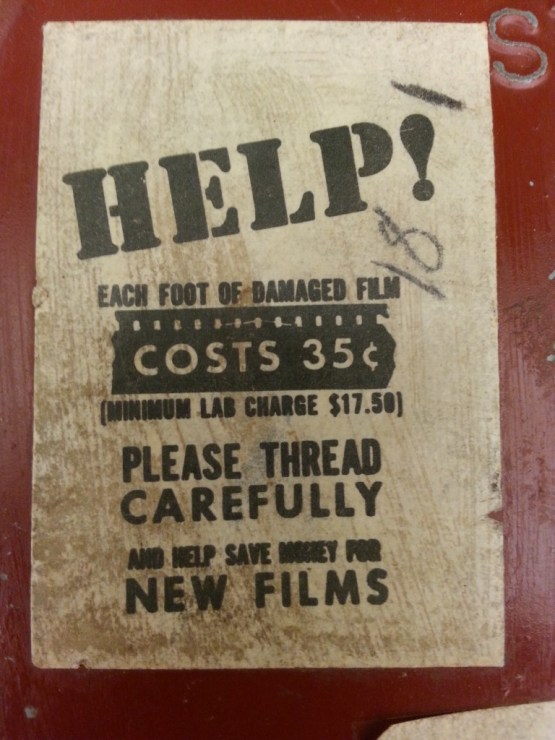 A sticker on the lid of a red film canister reads: help! each foot of scratched film costs 35 cents. Please wind carefully.