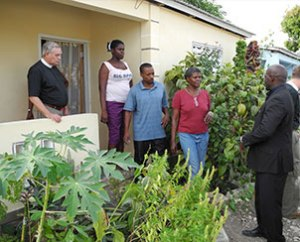 The first of 12 Haitian families to receive homes in Jacmel made possible by LCMS donors and partners — in collaboration with the Evangelical Lutheran Church of Haiti — visit with LCMS Director of Disaster Response Rev. Glenn F. Merritt, left, and Lophane Laurent, right, who facilitated an LCMS sanitary-latrine and water-well project in Haiti. This was at the time of the Jan. 14-15, 2012, dedication of three Lutheran villages in the island nation. (LCMS Communications/Al Dowbnia)
