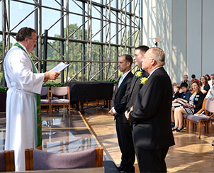 Synod President Rev. Dr. Matthew C. Harrison, left, installs three new staff members during the Aug. 19 chapel service at the LCMS International Center in St. Louis.  Left to right, they are Mark Cannon, senior vice-president for Finance and Administration for the LCMS Foundation; the Rev. Michael Meyer, manager of Distaster Response for the LCMS; and Terry L. Schmidt, the LCMS director of School Ministry. (LCMS Communications/Frank Kohn)