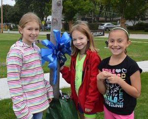"""Three third-grade students pose for a photo after tying a blue ribbon to a tree outside St. Peter Lutheran School, Arlington Heights, Ill., during an all-school celebration of St. Peter's """"National Blue Ribbon School"""" status, which was announced Sept. 24, 2013. (St. Peter Lutheran School)"""