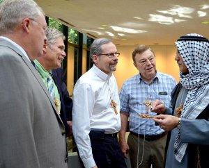 The Rev. Nabil S. Nour, right, the Synod's new fifth vice-president from Armour, S.D., wears his native Palestinian clothing as he talks with several fellow LCMS Council of Presidents (COP) members about the features of an olive-wood cross centered with a dove that he gave each council member during his opening devotion for the Sept. 20-24 COP meeting in St. Louis. From left, they are Third Vice President Rev. Daniel Preus, Second Vice-President Rev. Dr. John C. Wohlrabe, Northern Illinois District President Rev. Dan P. Gilbert and Indiana District President Rev. Dr. Daniel P. May. (LCMS Communications/Frank Kohn)