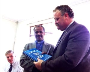 In Ethiopia, LCMS President Rev. Dr. Matthew C. Harrison, right, receives a book on the history of the Mekane Yesus Seminary of the Ethiopian Evangelical Church Mekane Yesus (EECMY) from EECMY  President Rev. Dr. Wakseyoum Idosa. At left is LCMS missionary Rev. Dr. Carl Rockrohr, dean of the School of Theology at the seminary. (Albert B. Collver III)