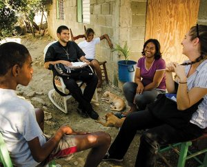 Vicar Gustavo Arturo Maita (second from left), a student from Concordia Seminary Argentina and a member of the Lutheran Church of Venezuela, conducts one of his regular visits with village residents in Palmar Arriba, Dominican Republic. (LCMS Communications/Pamela Nielsen)