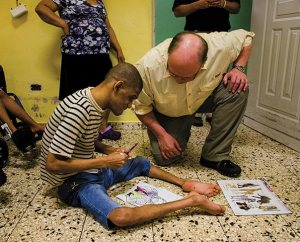 LCMS Board for International Mission (BIM) member John Edson, right, helps a resident of a government-run institution for the mentally and physically disabled in Santo Domingo, Dominican Republic — one of several mercy-outreach projects served by the LCMS missionary team in the country. During their February 22-26 visit there, the BIM toured a number of those sites. (LCMS Communications/Pamela Nielsen)