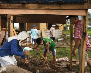 With the help of LCMS disaster dollars, Cash-for-Work builders construct a well (foreground) and parsonage (rear) next to Christ Lutheran Church in Mahayag, Philippines (LCMS Communications/Erik M. Lunsford)