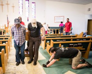 Volunteers and pastors from several Lutheran congregations help remove the organ, carpet and pews from the flooded sanctuary of St. Matthew Lutheran Church in Pensacola, Fla., on May 3. The church was one of four LCMS churches in the area that flooded April 30 during the highest rainfall ever recorded in the port city. More than 3,000 homes flooded and most of the homeowners did not have flood insurance.  (LCMS Communications/Erik M. Lunsford)