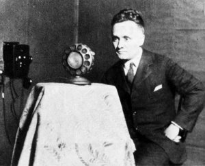 "The Rev. Dr. Walter A. Maier, the station's first ""Gospel voice,"" poses with a microphone from that early era."