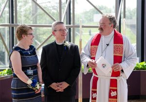 LCMS President Rev. Dr. Matthew C. Harrison, right, welcomes new Chief Mission Officer Rev. Kevin D. Robson and his wife, Peg, following Robson's May 18 installation service in St. Louis. (LCMS/Frank Kohn)