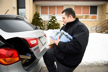 With arms full of Bibles and witnessing materials to distribute, Vicar David Blas loads his vehicle at St. John Lutheran Church in Plymouth, Wis.