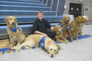 "The Rev. Robert C. Trueblood, pastor of St. James Evangelical Lutheran Church in Northrop, Minn., poses with six of the 10 ""comfort dogs"" from Lutheran Church Charities that visited the town after fire destroyed the church building. (Elaine Tessler/Immanuel Lutheran Church, Belvidere, Ill.)"