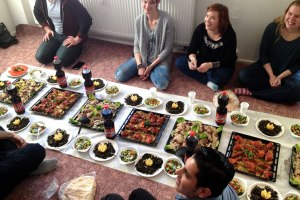Concordia University System students studying abroad in Germany this spring enjoy a meal hosted by a group of Syrian refugees after a meeting that gave the students a new perspective on the refugees' circumstances. (Courtesy of Renata Mayrhofer)