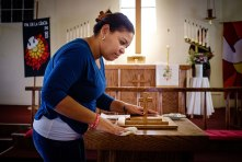 Yadira Lozano Odio, a new Cuban immigrant to the United States, gently cleans the baptismal font in preparation for several baptisms at San Pablo Lutheran Church on Sunday, May 22.