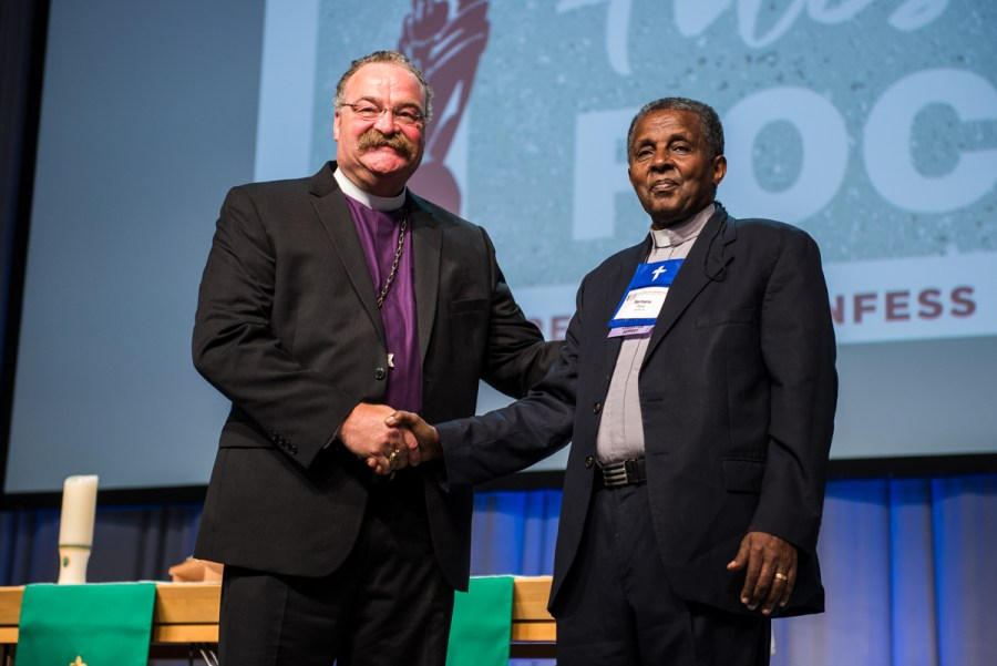 "LCMS President Rev. Dr. Matthew C. Harrison, left, thanks the Rev. Berhanu Ofgaa, general secretary of the Ethiopian Evangelical Church Mekane Yesus, for his July 13 convention essay, ""Upon This Rock: Rejoice."" (LCMS/Frank Kohn)"