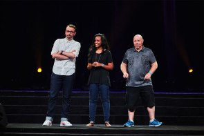 """Emcees, from left, the Rev. Matt Popovits, Abi Tesfaye and the Rev. Jeffrey Meinz explain to participants that """"true joy is found in Christ alone"""" at an evening Mass Event in the Mercedes-Benz Superdome. (Matthew Boness)"""