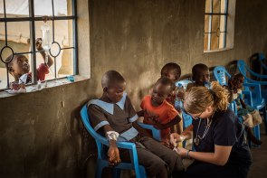 Children gather to watch as Sarah Kanoy treats a girl with low blood pressure.