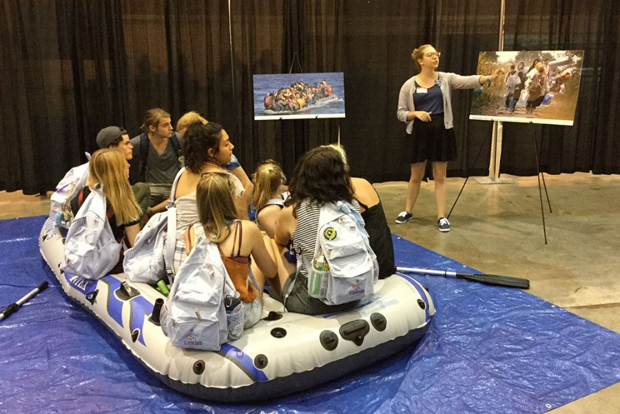 Participants cram into a raft while hearing from Lutheran Immigration and Refugee Service (LIRS) summer intern Pam Launius about the dangers of attempting to cross the sea. This was one element of the LIRS simulation experience at the 2016 LCMS Youth Gathering. (LIRS/Cecilia Pessoa)