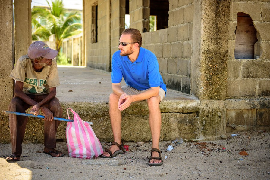 The Rev. Duane Meissner, LCMS missionary to Belize, stops to talk with an elderly man on the beach.