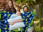Journey Hudson hugs his Pillow Pet as his parents, Michelle and Parker Hudson, hold the blanket made by Martin Luther High School students.