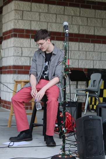 "Sophomore Aidan Gurley waits for his bandmates, Kylie Woods and Gwen Brandenborg, to set up their instruments before performing ""No Fun"" by Joji."