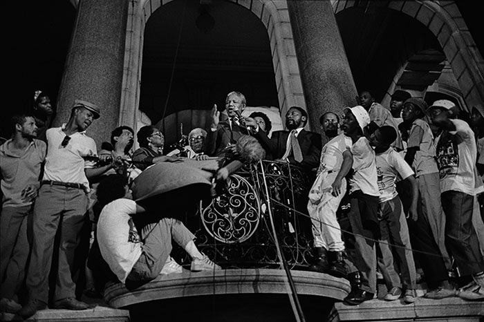 Photo by CHRIS LEDOCHOWSKI Nelson Mandela makes his first speech to the nation from the balcony of the Cape Town City Hall after his release from prison, Western Cape. 1990 Courtesy UCT Libraries Special Collections""