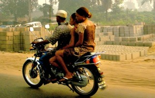 Okada motorcycle driver and passengers in Nigeria.