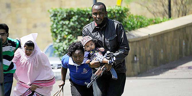 A policeman carries a baby to safety during the Westgate shopping mall attack that left 67 people killed and 175 wounded.                        Photo by Simon Maina