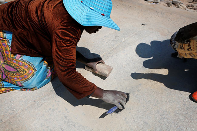 A woman gathering 'vhovho' (sand rich in gold particles) as part of her payment for pounding the gold-rich rock. Every particle or grain on the grinding rock is collected as it is believed to contain traces of gold. Women workers claim that they earn at least R500 up to R1 000 per bucket of this kind of sand. Nothing is wasted!